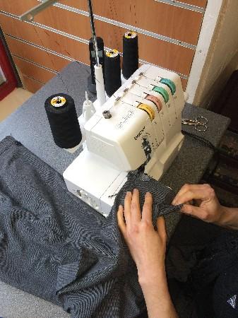 Pantalon de costume préparation ourlet à la surjeteuse.