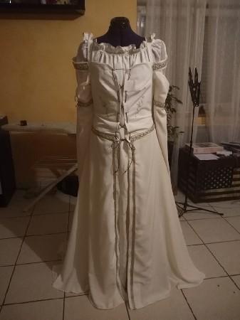 Cette jolie robe est en deux parties:<br /> une sous-robe en lin blanc cassé dont le col est relevé d'une collerette brodée à la main au point de feston. Les manche sont fermées par laçage aux poignets.<br /> La sur-robe est en tissus microfibre écru, le haut de la robe est doublé lin et brodé à la main<br /> Les manches sont doublée en soie champagne.<br /> La robe est bordée de galons dorés, le laçage se fait sur le devant.
