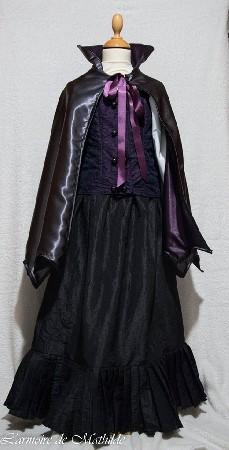 Déguisement de vampire victorien en taille 10 ans composé d'une cape en satin de polyester gris doublée de violet, une jupe en taffetas de polyester froissé noir et d'un faux gilet en taffetas de polyester violet couvert de dentelle noir avec chemise blanche à manches gigot. Vendu sur littlemarket.
