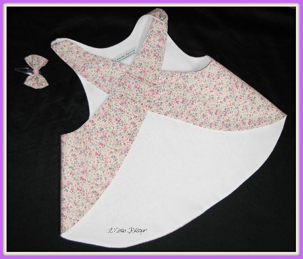 Tablier crois&eacute; dans le dos pour demoiselle de 2/3 ans. <br /> R&eacute;alis&eacute; dans un coton Liberty rose &agrave; petites fleurs roses et mauves. Il est doubl&eacute; dans un tr&egrave;s beau coton blanc &agrave; l&eacute;g&egrave;re brillance. <br /> Fermeture sur les &eacute;paules par deux pressions nacr&eacute;s blanches. <br /> Pour les cheveux, une ravissante petite barrette &quot;clic-clac&quot; avec son petit nœud en coton Liberty et ruban rose en son milieu. <br /> A porter d&#039;urgence d&egrave;s les premiers rayons de soleil !